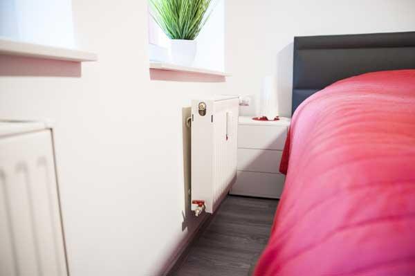Heizung und Bett im Schlafzimmer einer Souterrainwohnung