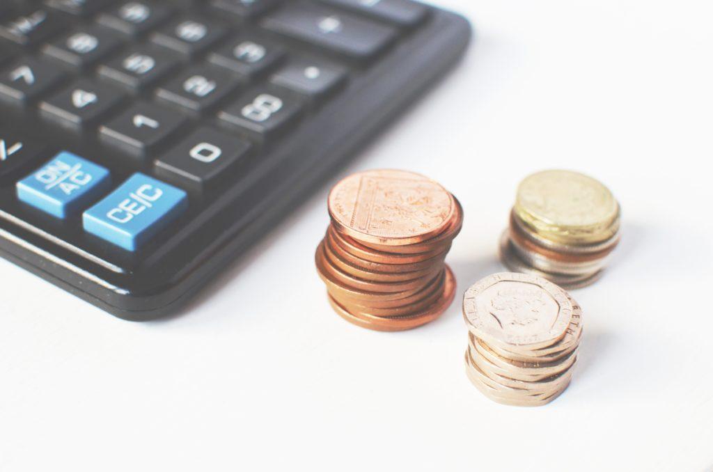 Taschenrechern mit Münzen daneben