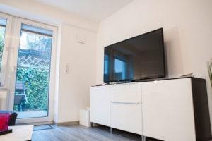 Souterrainwohnung Wohnzimmer mit Fernseher und Schrank